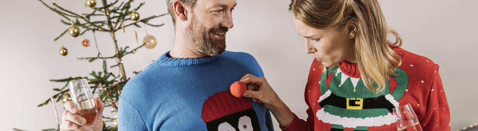 Ein Mann und eine Frau stehen vor einem Weihnachtsbaum. Beide tragen Pullover mit Weihnachtsmotiven. Sie halten Sektgläser in den Händen.