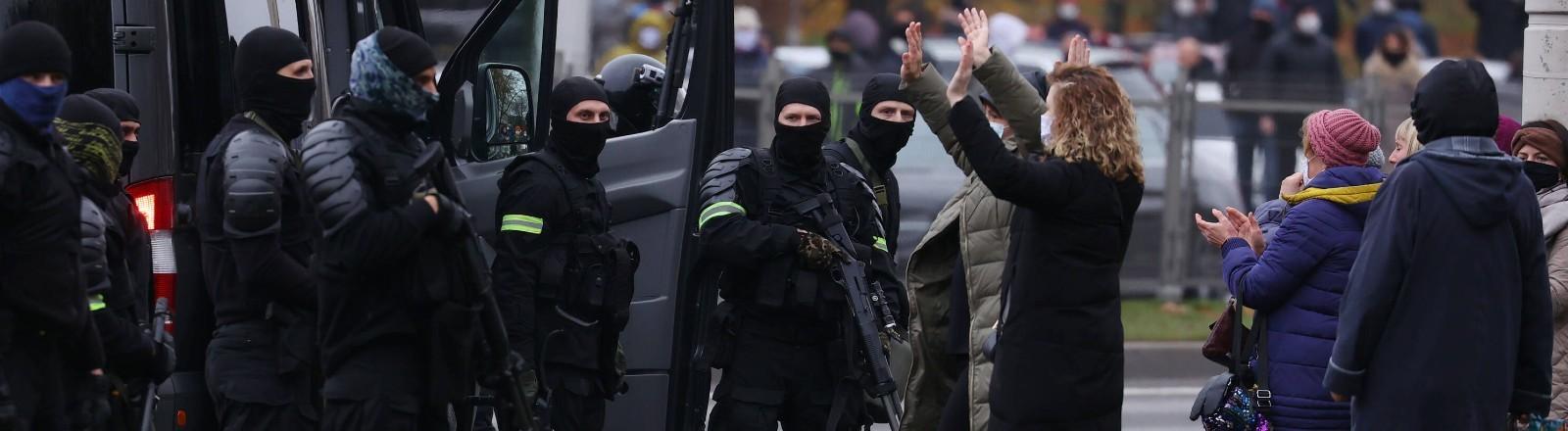 Polizisten stehen mit Waffen vor Demonstrierenden bei einem Protest am 15.11.2020.