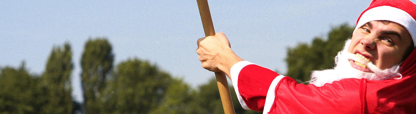 Mann mit angehängtem Weihnachtsmann-Bart und Nikolausmütze mit Sense in der Hand zieht Grimasse und gestikuliert