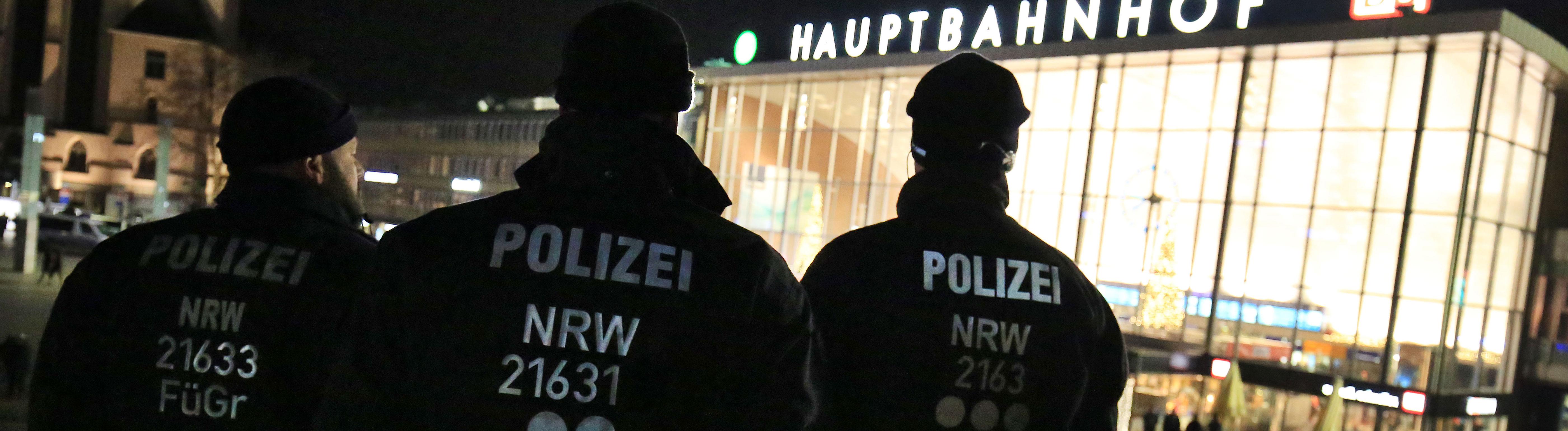 Drei Polizisten stehen (31.12.2016) in Köln vor dem Hauptbahnhof. Die drei sind von hinten zu sehen, wie sie Richtung Bahnhof blicken; Foto: dpa