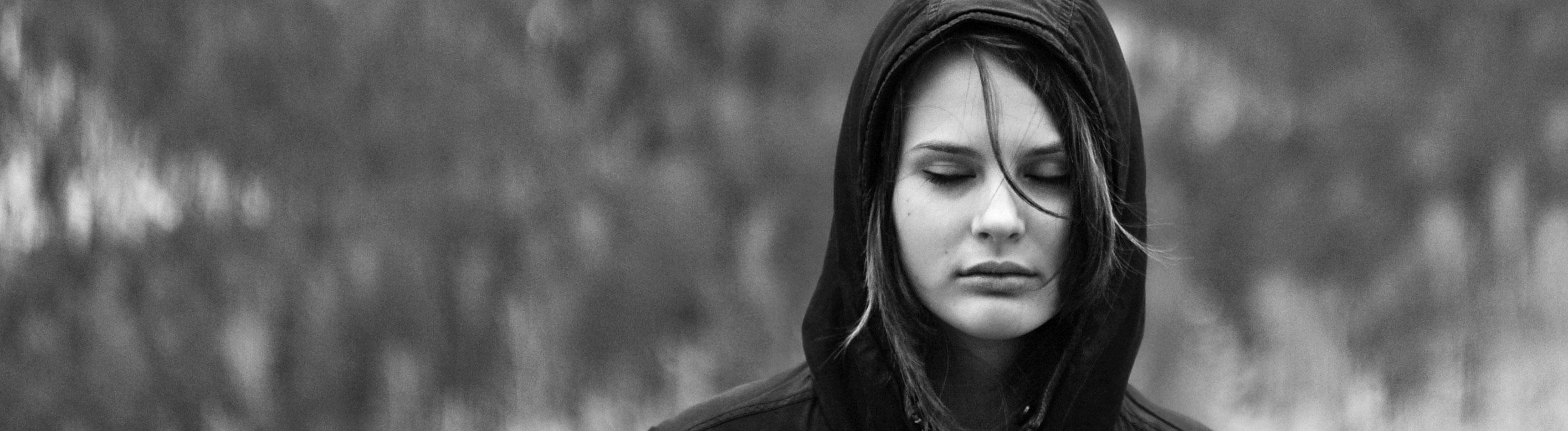 Schwarz-weiß Foto zeigt eine Frau mit geschlossenen Augen. Sie steht draußen. Trägt eine Jacke und hat die Kapuze hochgezogen.