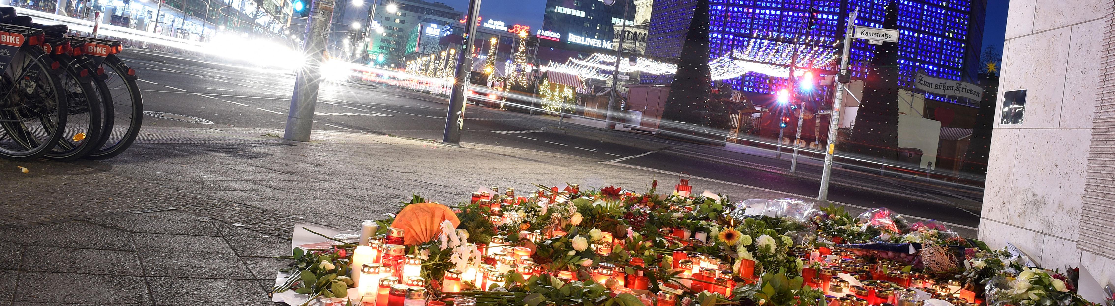 Autos fahren am 22.12.2016 am Anschlagsort in der Nähe der Gedächtniskirche in Berlin vorbei. Menschen haben Blumen abgelegt; Foto: dpa