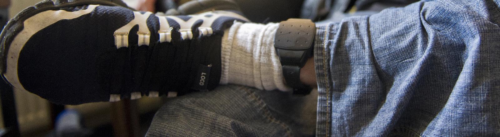 Ein Mann trägt eine elektronische Fußfessel.