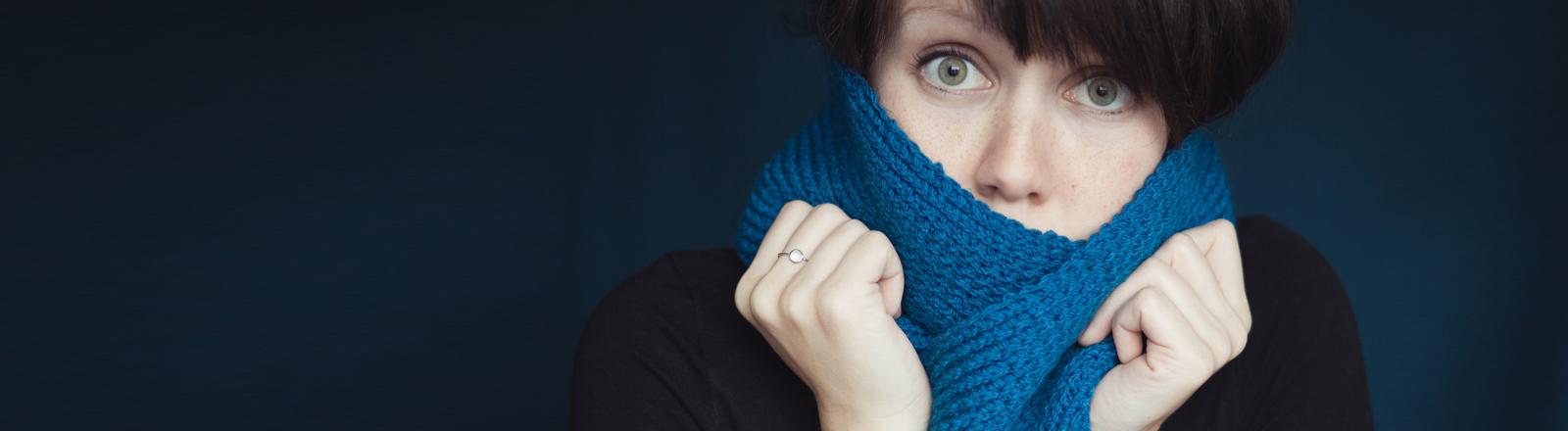 Eine Frau kuschelt sich in ihren Schal.