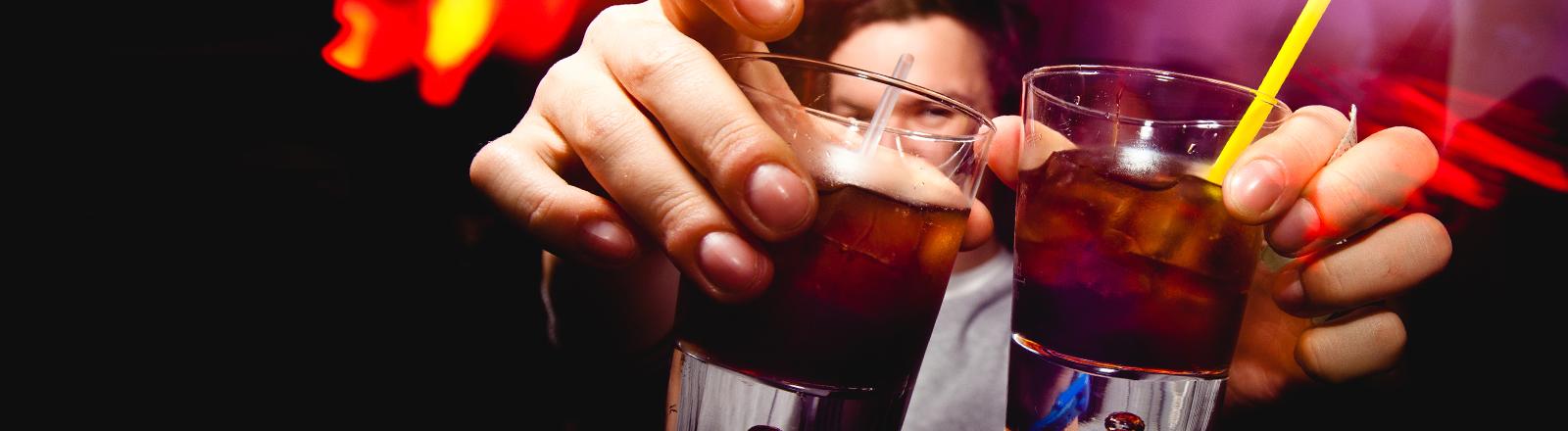 Ein Barkeeper präsentiert zwei Cocktails.