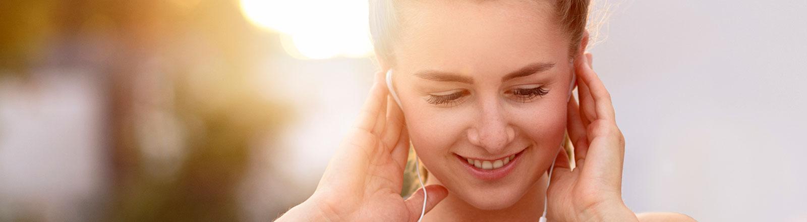 Junge Frau hört Musik im Sonnenschein