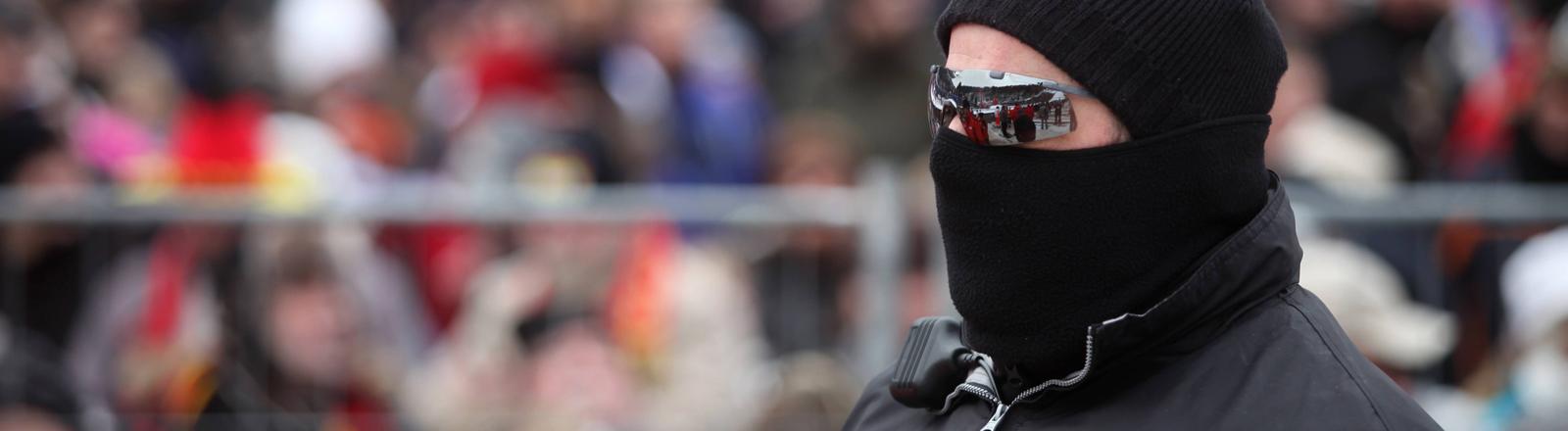 Ein Sicherheitsmann mit Sonnenbrille und Skimaske.