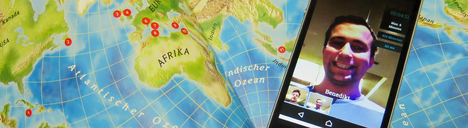 Ein Handy mit der App Oroboo liegt auf einer Landkarte.