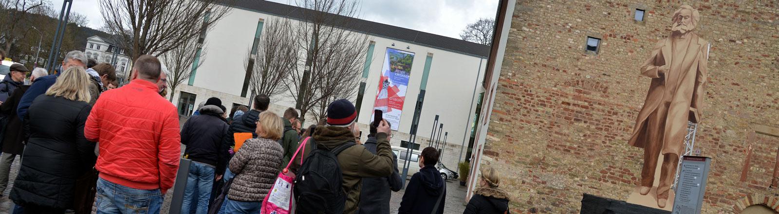 Passanten betrachten am 01.03.2017 in Trier einen hölzernen Schattenriss in Originalgröße einer geplanten Karl Marx-Statue, die 6,30 Meter hoch werden soll; Foto: dpa