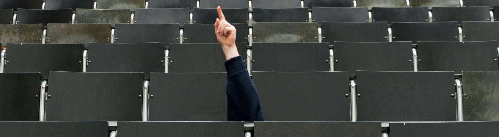 Leere Reihen in einem Hörsaal. In einer der Reihen wird eine Hand nach oben gestreckt mit ausgestrecktem Zeigefinger.