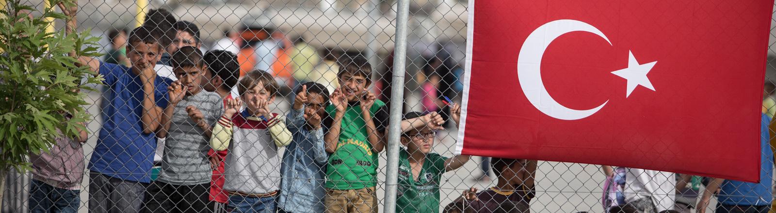 In einem Flüchtlingslager im türkischen Gaziantep stehen Kinder hinter einem Zaun. Am Zaun hängt die türkische Flagge. Kanzlerin Merkel besuchte am 23.04.2016 das Lager; Foto: dpa