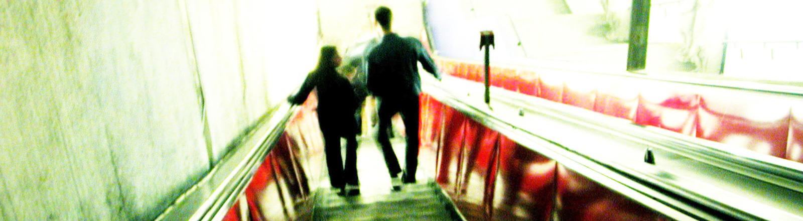 Eine Frau und ein Mann fahren eine Rolltreppe nach unten. Das Bild ist unscharf.