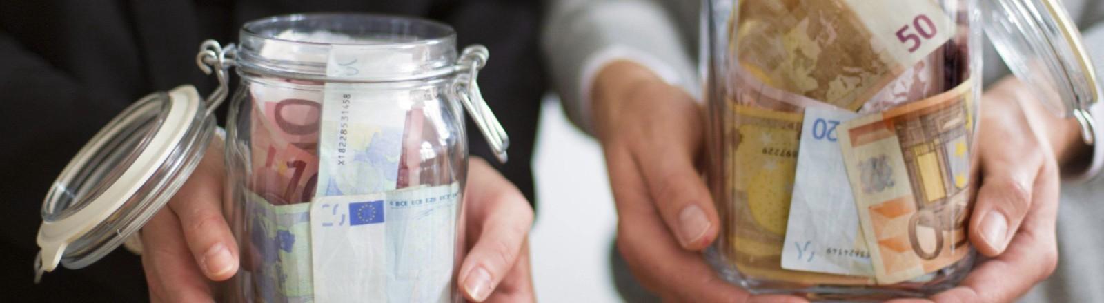 Frau und Mann halten unterschiedlich volle Gläser mit Geldscheinen in den Händen