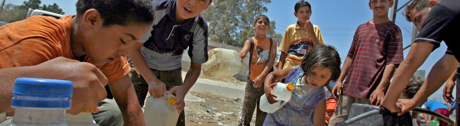 Jugendliche im Gaza-Streifen füllen Wasser ab