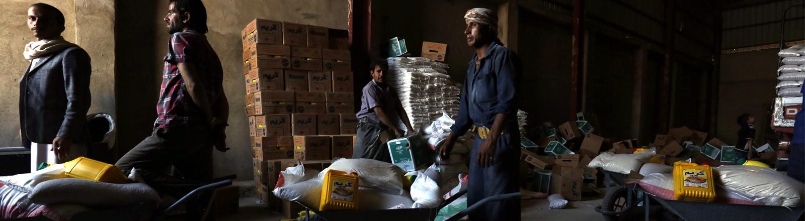Männer mit Schubkarren fahren Nahrungsmittel aus einer Halle im Jemen