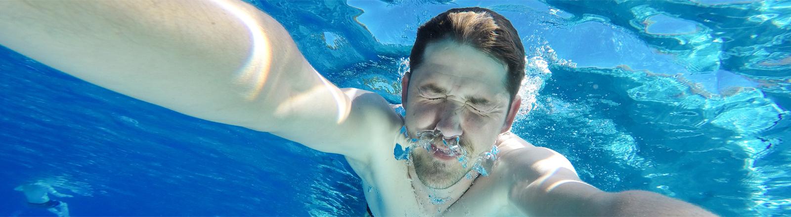 Tauchender Mann im Schwimmbad