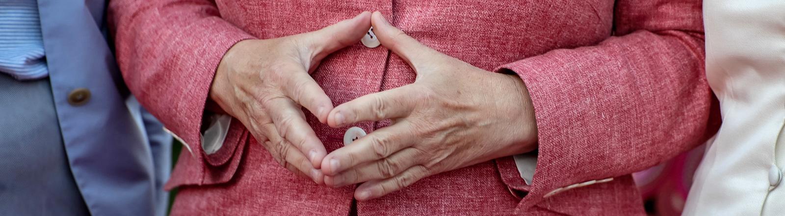 Angela Merkel hat ihre Hände zur Raute geformt.