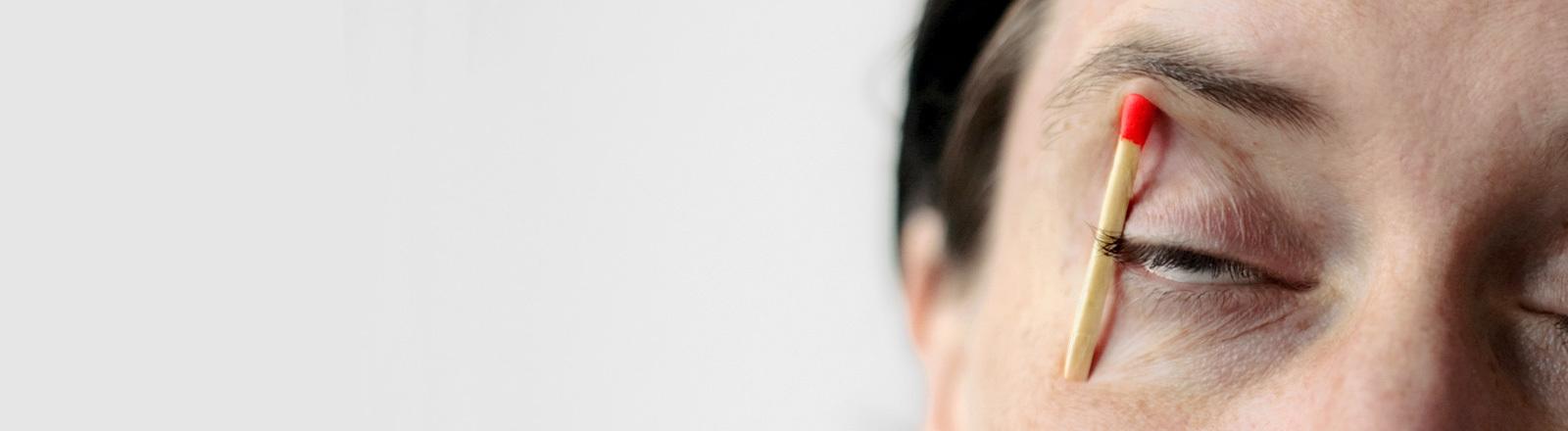 Eine Frau hat sich ein Streichholz unter die rechte Augenbraue geklemmt.