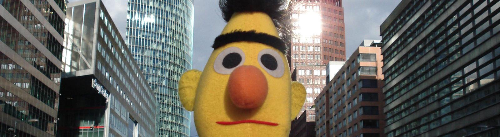 Die Figur Bert aus der Sesamstraße. Im Hintergrund Hochhäuser.