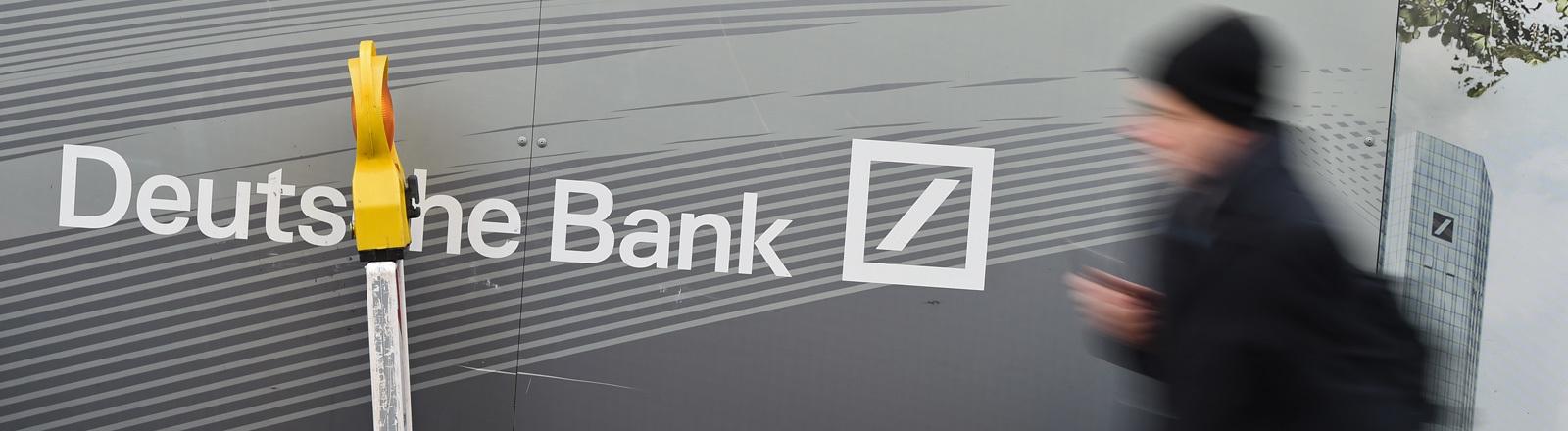 Ein Mann geht an einem Baustellenzaun mit dem Schriftzug der Deutschen Bank vorbei.