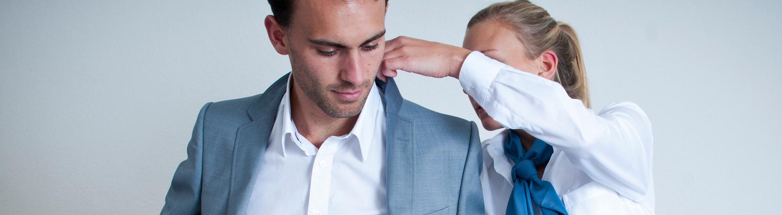 Ein Mann zieht seine Anzugsjacke an. Eine Frau hilft ihm und macht den Kragen ordentlich.