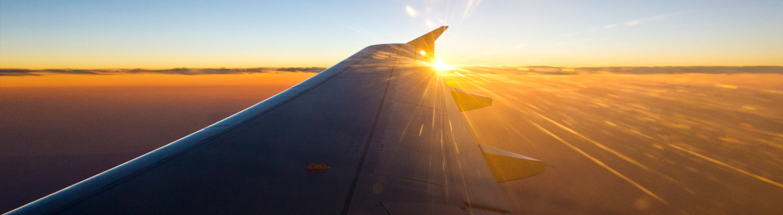 Ein Flugzeugflügel an dessen Tragflächenspitze die Sonne über den Horizont glüht