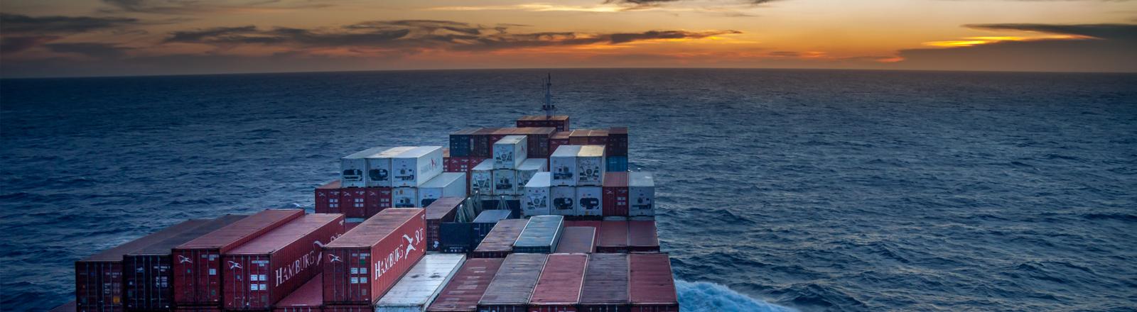 Ein Containerschiff fährt in den Sonnenuntergang