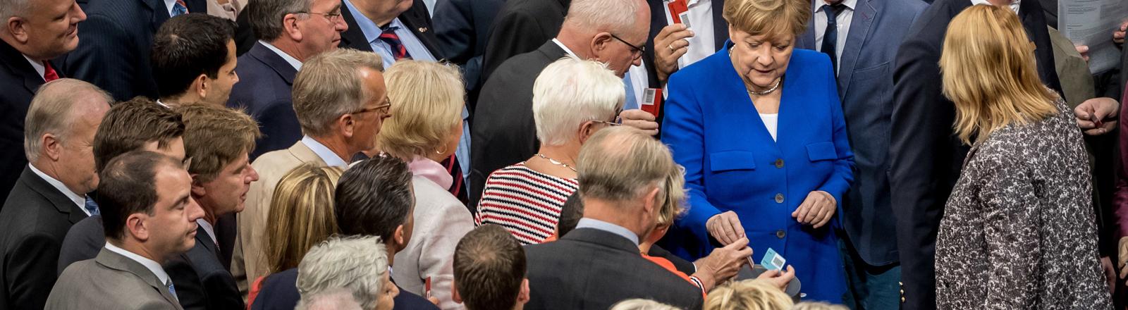 """Bundeskanzlerin Angela Merkel (CDU) wirft am 30.06.2017 im Bundestag in Berlin im Plenum ihre """"NEIN"""" Stimmkarte ein."""