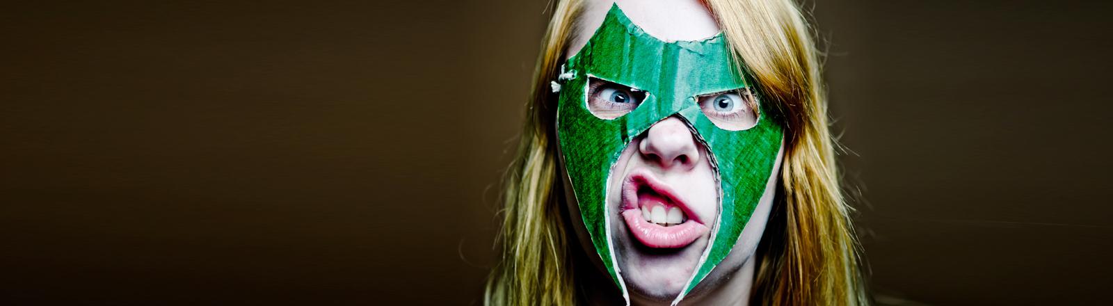 Mensch mit wütender Grimasse und grüner Maske vorm Gesicht