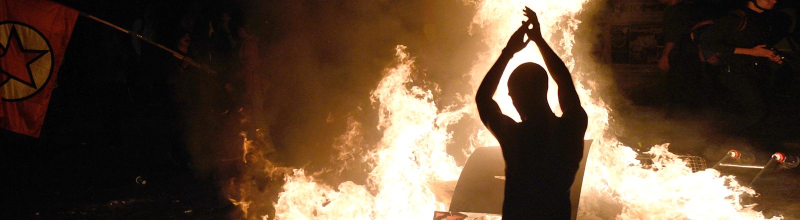 Demonstrant wirft im Hamburger Schanzenviertel Holzstücke in brennende Barrikade vor der Roten Flora