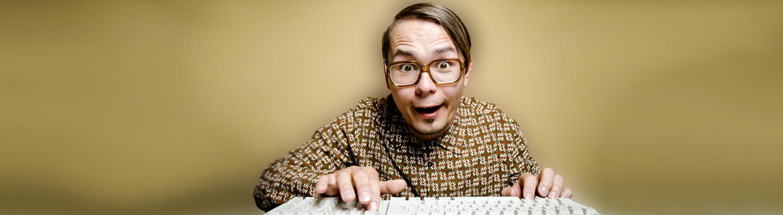 Mann mit Hornbrille an altem Computer