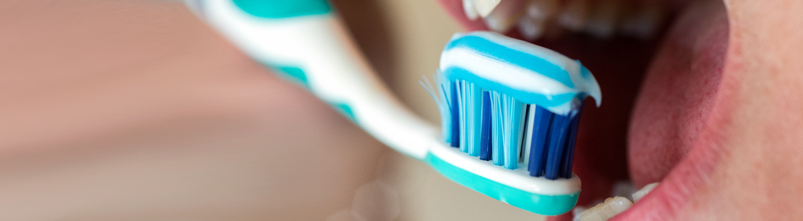 Zahnbürste mit Zahnpasta setzt zum Putzen an