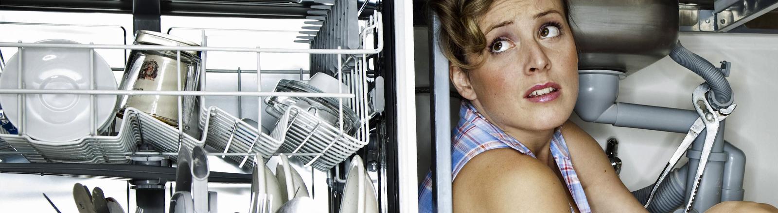 Eine Frau verzweifelt an der Waschmaschine.