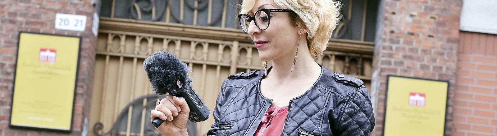 Die Lärmforscherin Antonella Radicchi steht vor einem Backsteingebäude und hält ein Mikrofon in der Hand.