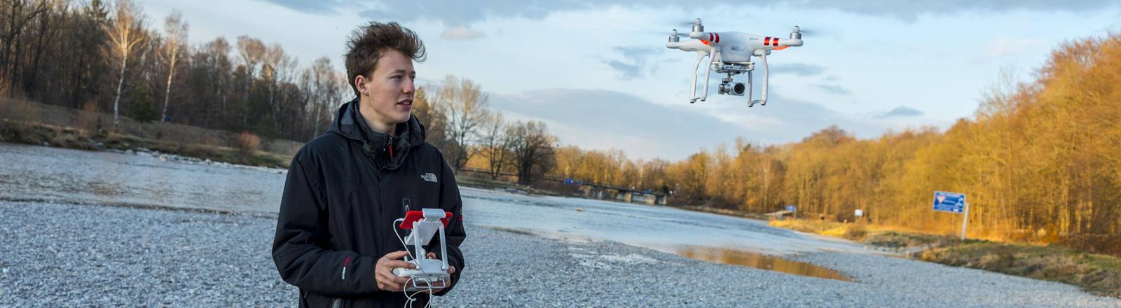 Ein Mann lässt eine Drohne fliegen, im Hintergrund ist Wald auf den Sonnenschein fällt.