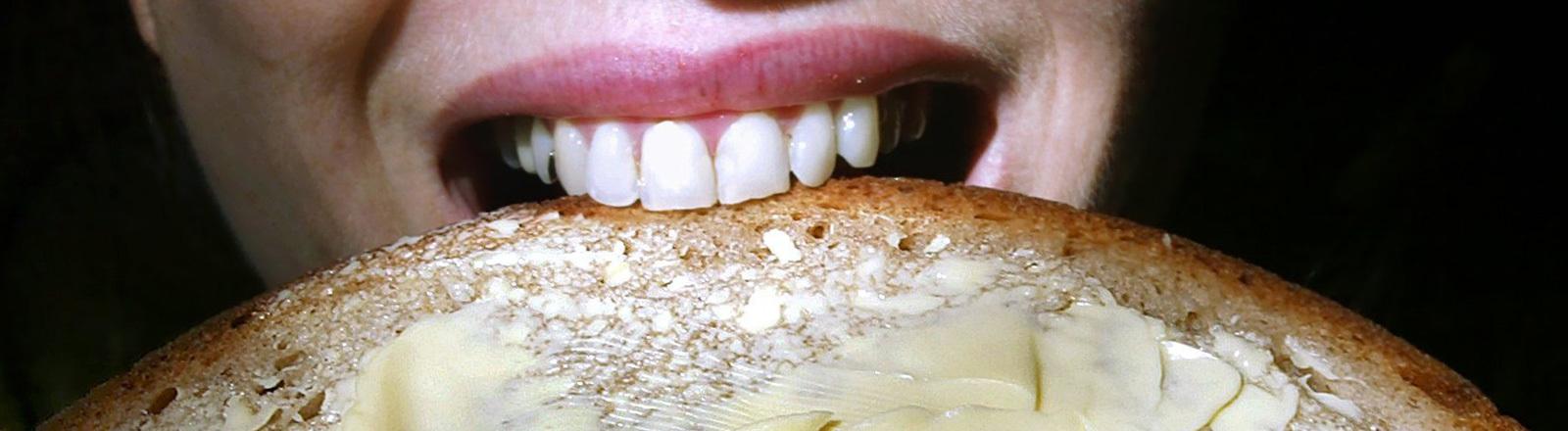 Eine Frau beißt in ein Butterbrot. Nur ihr Mund ist zu sehen; Foto: dpa
