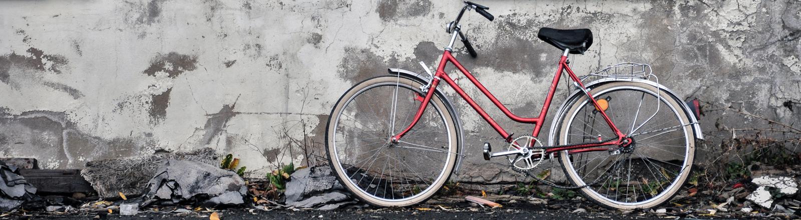 Ein Fahrrad steht an einer Wand.