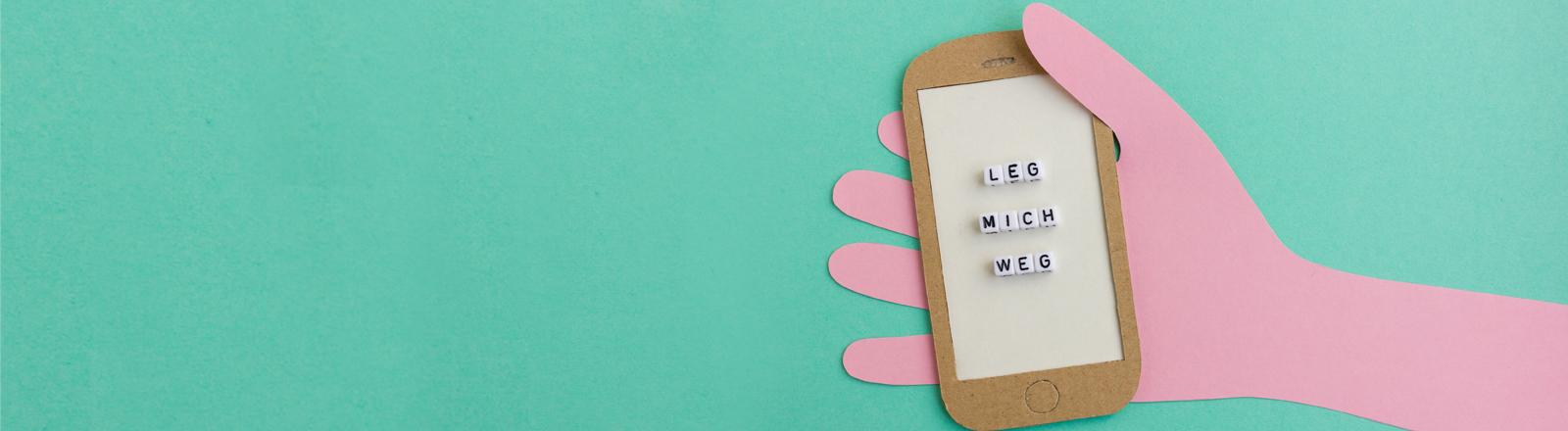 """Ein Papp-Handy mit dem Schriftzug """"Leg mich weg""""."""