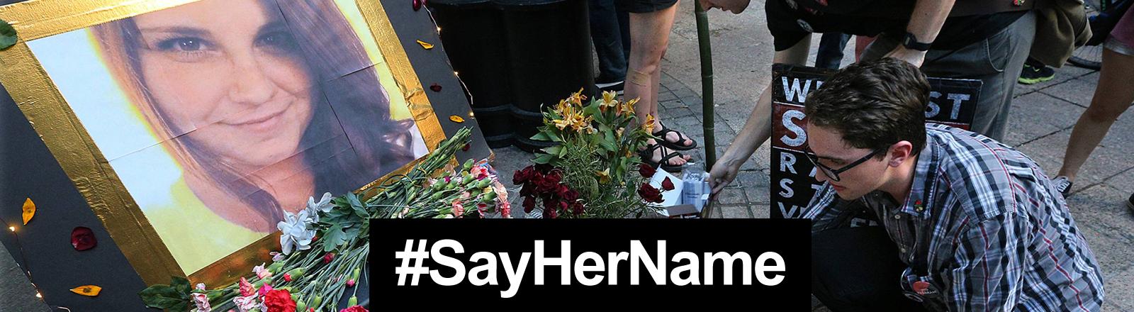 Vor einem Bild von Heather Heyer werden Blumen niedergelegt und Grabkerzen entzündet