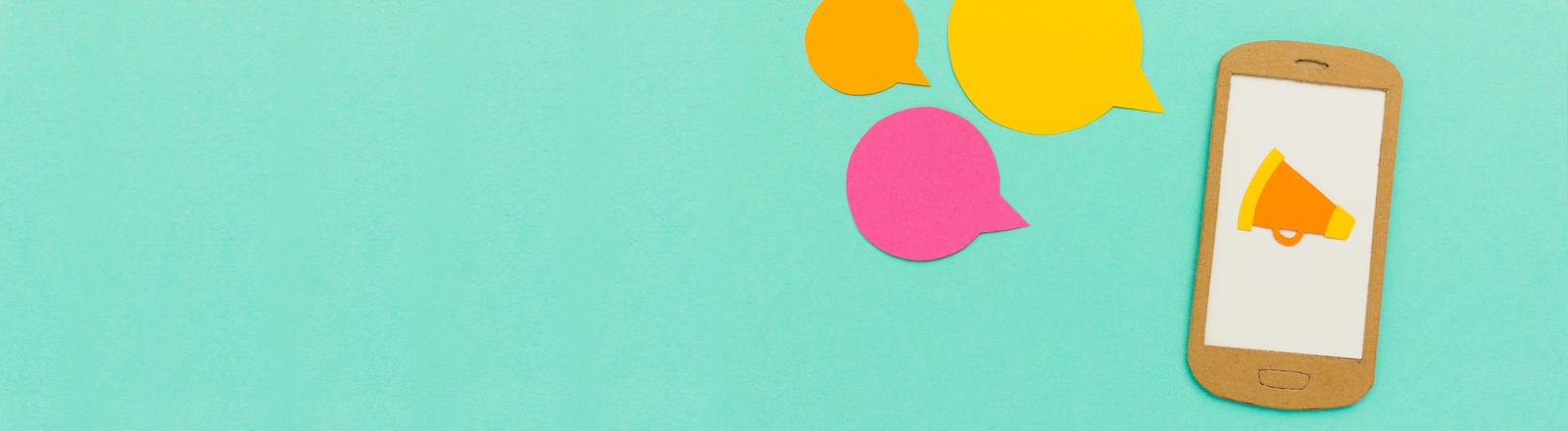 Ein Smartphone aus Papier gebastelt, darauf eine kleine Flüstertüte und Sprechblasen drumherum