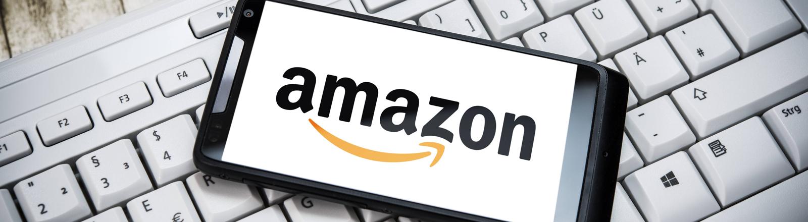 Ein Smartphone mit dem Amazon-Logo auf einer Tastatur