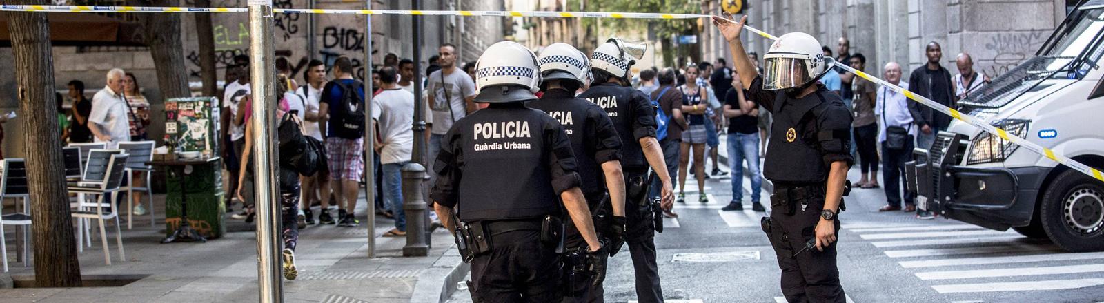 Polizisten verlassen den Tatort und gehen unter einem Absperrband hindurch