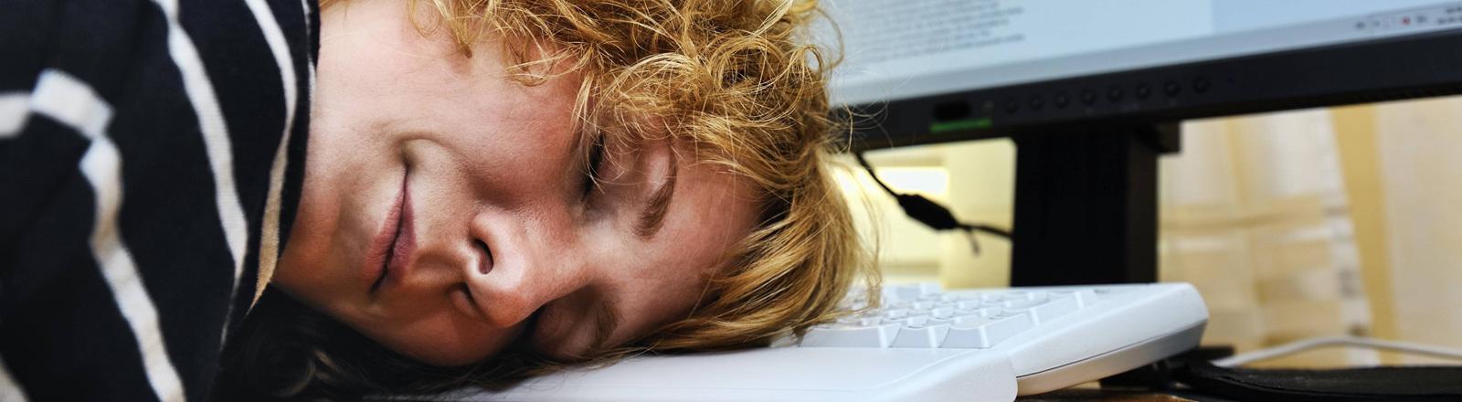 Eine Frau hat ihren Kopf auf eine Computertastatur gelegt und schläft.