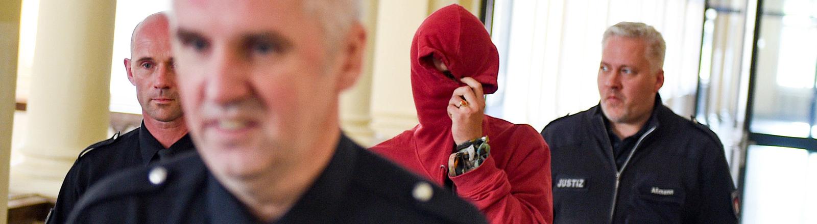 Justizbeamte führen am 28.08.2017 in Hamburg im Strafjustizgebäude einen 21-jährigen Angeklagten aus den Niederlanden zum Gerichtssaal; Foto: dpa