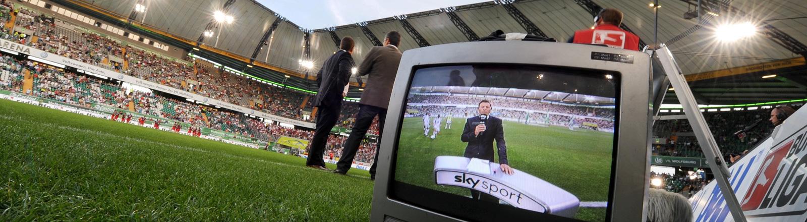 Ein Fernsehgerät steht auf dem Rasen eines Fußball-Stadions. Auf dem Fernseher läuft eine Sendung des Bezahlsenders SKY Sport; Foto: dpa