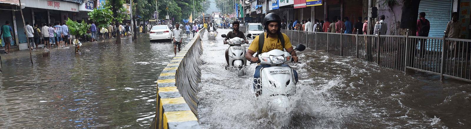 Mumbai kämpft mit Regenmassen. Eine Straße steht komplett unter Wasser, zwei Mopedfahhrer bahnen sich den Weg (30.08.2017) (.