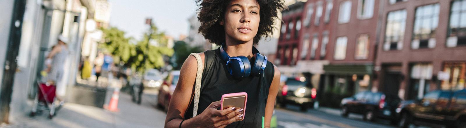 Eine Frau läuft eine Straße hinunter, sie hält ein Smartphone in der Hand.