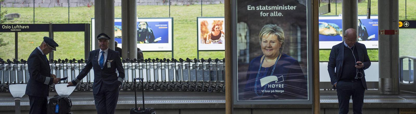 Auf einem Bahnsteig warten Fahrgäste. Zwischen ihnen steht ein Wahlplakat.