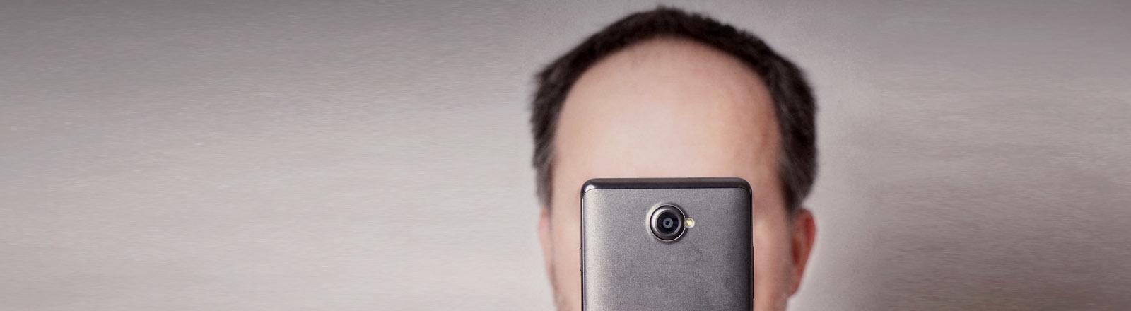 Mann hält Smartphone vors Gesicht