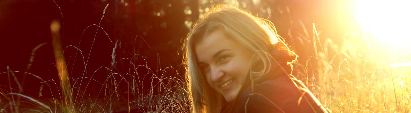 Junge Frau tankt Herbstsonne